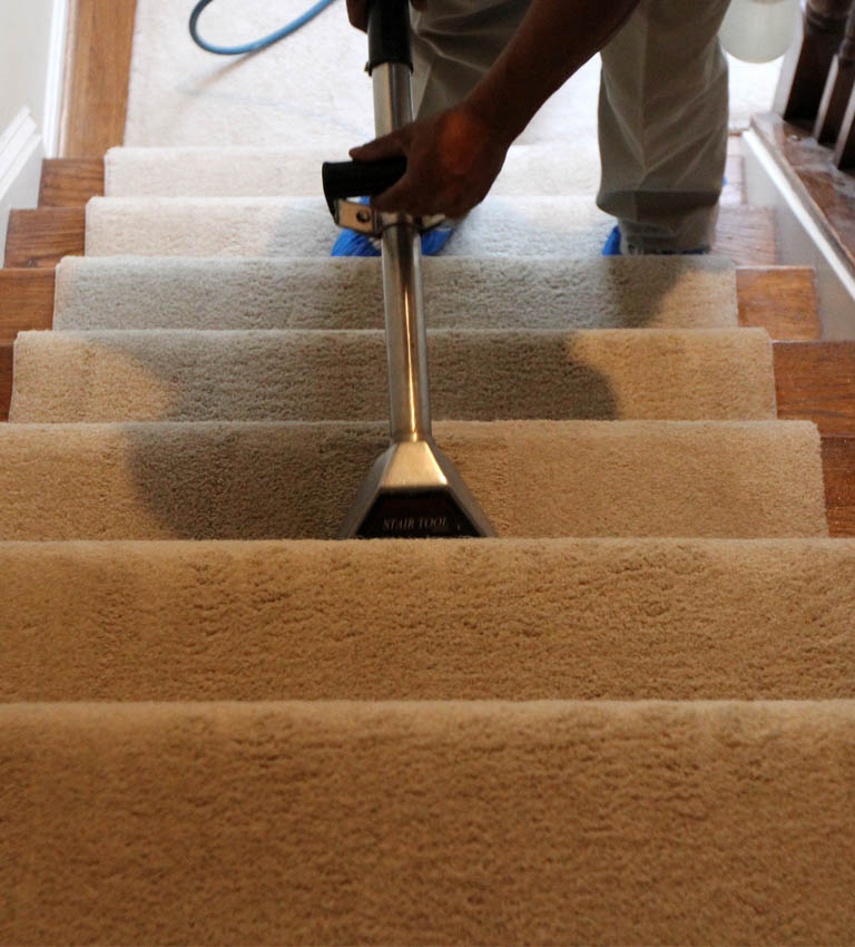 Man cleaning carpet on stairs